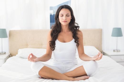Calm brunette doing yoga on bed